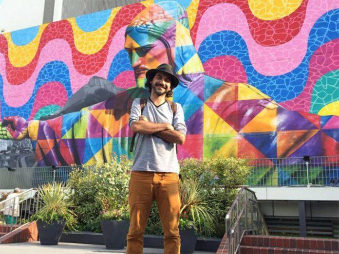 O grafiteiro em frente ao mural criado na capital do Japão