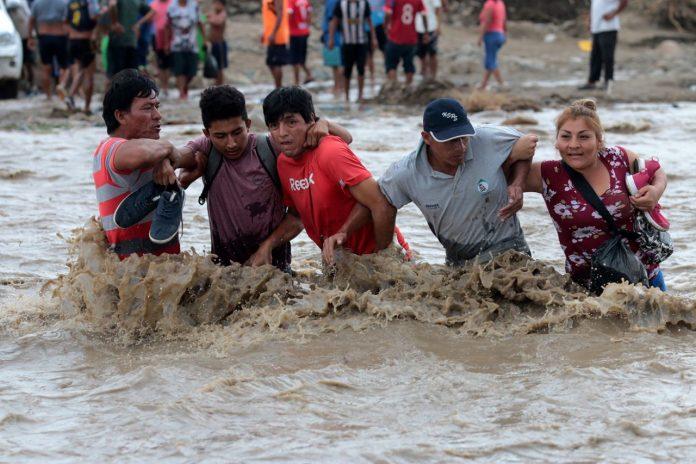 Moradores cruzam o rio Viru após queda da ponte