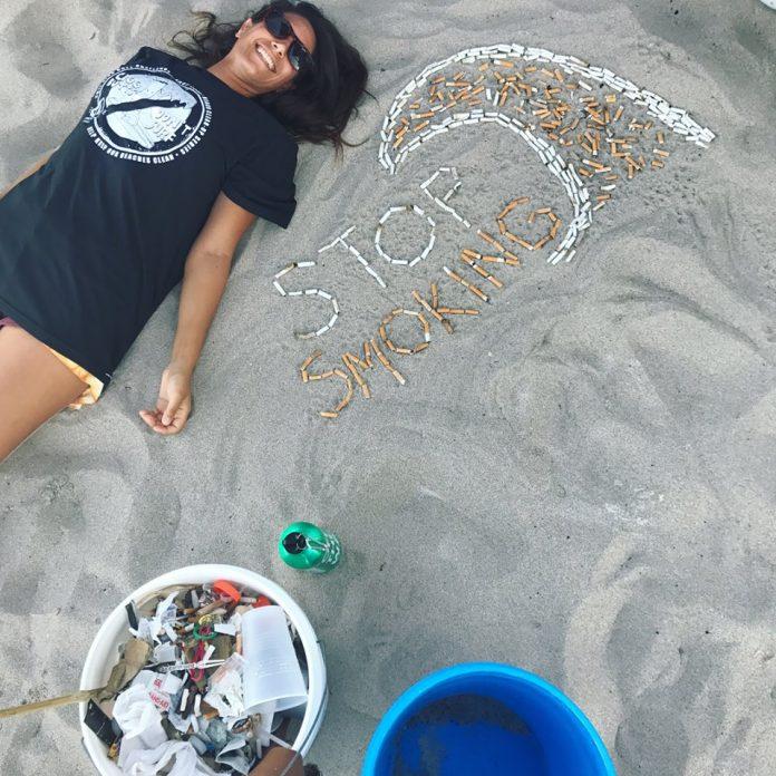 Voluntária posa ao lado das pontas de cigarro encontradas na praia de Deerfield Beach