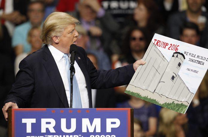 Donald Trump em sua campanha presidêncial em 2016, usou um poster feito por um apoiador na audiência enquanto aprestava seu plano para construir o muro na fronteira com o México