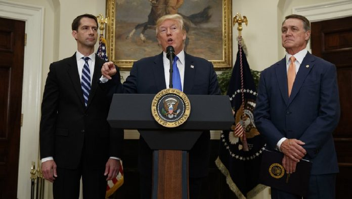 Trump ladeado pelos senadores Tom Cotton e David Perdue
