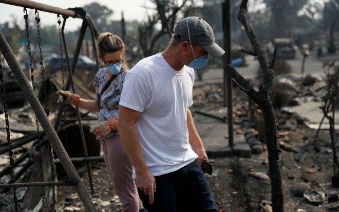 Moradores tentam recuperar documentos em casa destruída pelo fogo FOTO REUTERS