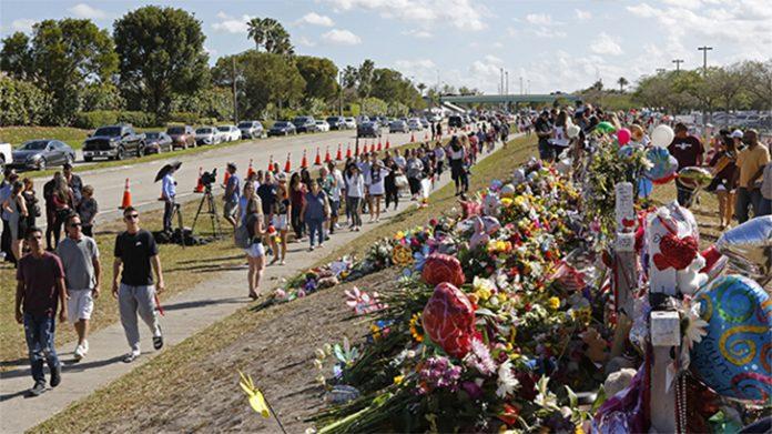 Pais e alunos caminham próximo ao memorial para as vítimas do massacre na Marjory Stoneman Douglas High School (Foto: David Santiago/Miami Herald/TNS/Getty Images)