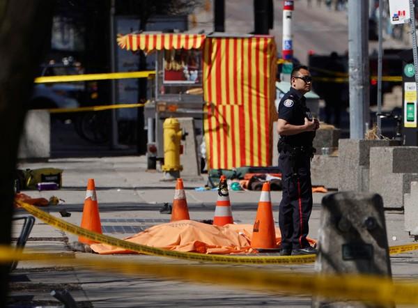 Policial é visto ao lado de uma vítima no local do atropelamento FOTO Carlo Allegri Reuters