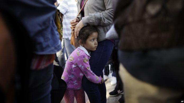 Criança mexicana na fila para aguardar pedido de asilo na fronteira FOTO AP