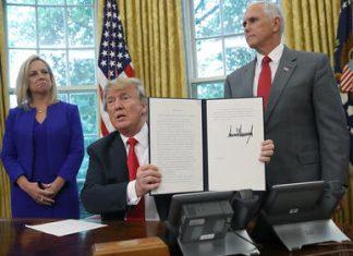 O presidente mostra decreto assinado acompanhado pela secretária do Homeland Security, Kirstjen Nielsen e do vice-presidente Mike Pence. FOTO: Win McNamee Getty Images