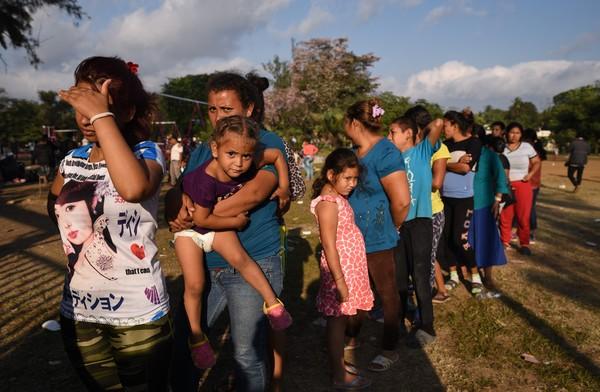 Imigrantes da América Central que participam da caravana em direção aos Estados Unidos fazem fila por comida em um campo de esportes em Matias Romero, Estado de Oaxaca, México. (Foto AFP Victoria Razo)