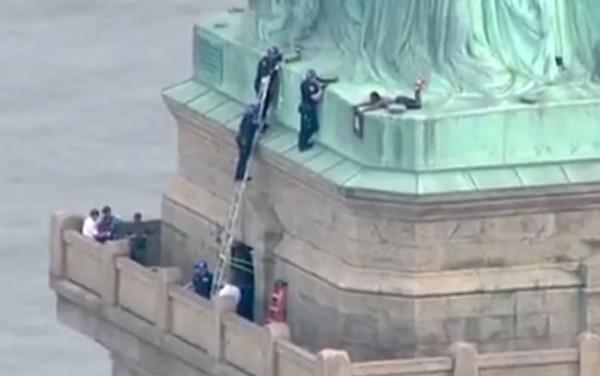 Imagem retirada de vídeo mostra policiais tentando convencer mulher a descer da base da Estátua da Liberdade