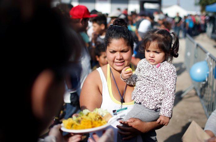 Imigrante com filha recebe neste domingo (23) prato de paella perto de abrigo temporário em Tijuana, no México — Foto Mohammed Salem Reuters