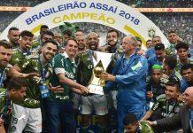 Jair Bolsonaro com a mão na taça de campeão conquistada pelo Palmeiras
