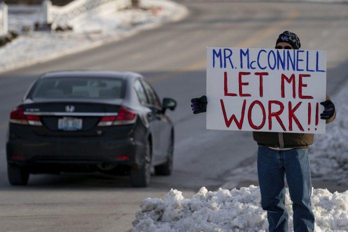 Funcionário da Agência de Proteção Ambiental dos EUA exibe cartaz perto do escritório do senador Mitch McConnell— Foto Bryan Woolston AP Photo