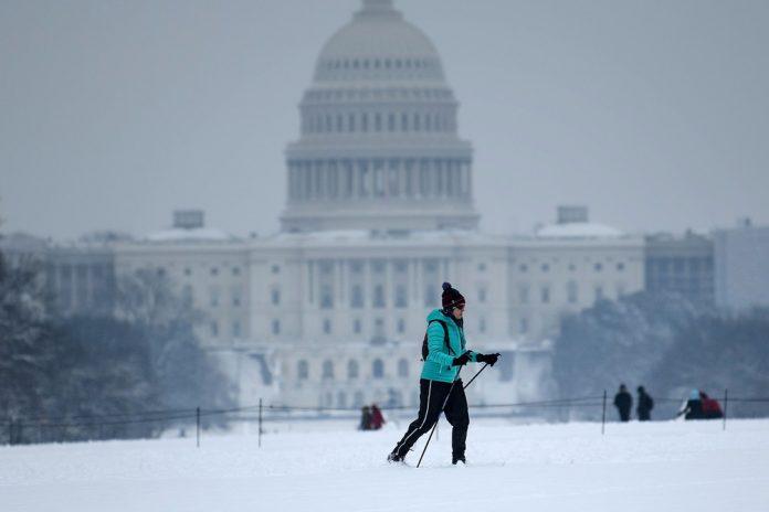 Homem esquia perto do Capitólio, em Washington, no domingo (13) — Foto Brendan Smialowski AFP