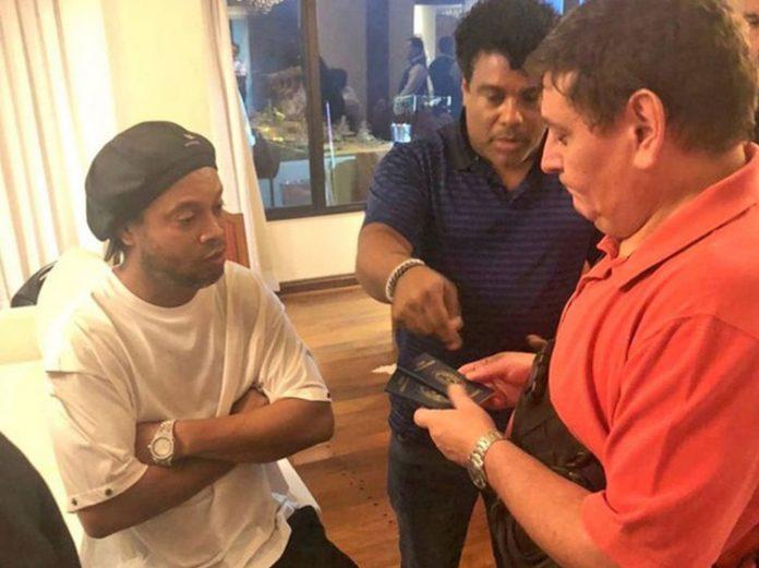 Autoridade paraguaia analisa passaportes de Ronaldinho Gaúcho e do irmão dele, Assis (Foto: Ministério Público Paraguai Reprodução)