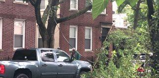 Moradores observam cabo de eletricidade caído em rua no Queens após a passagem da tempestade tropical Isaías