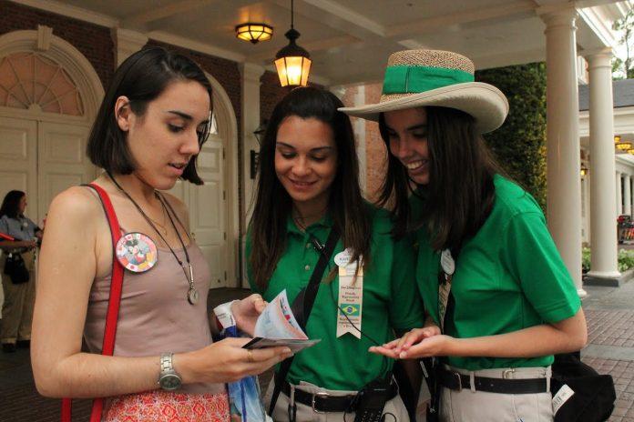 Funcionário brasileiro da Disneylândia orienta turista. Disney anunciou a demissão de 28 mil funcionários essa semana (Foto: Reprodução)