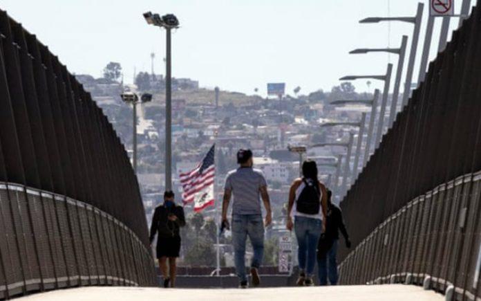 Pessoas usando máscaras cruzam a ponte sobre a rodovia na fronteira EUA-México em San Diego, Califórnia (Foto: Étienne Laurent/divulgação)