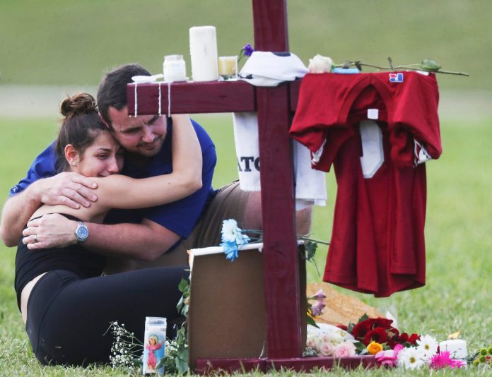 Familiares e amigos das vítimas se reuniram para prestar homenagens neste doming, 14 (foto: Reuters)