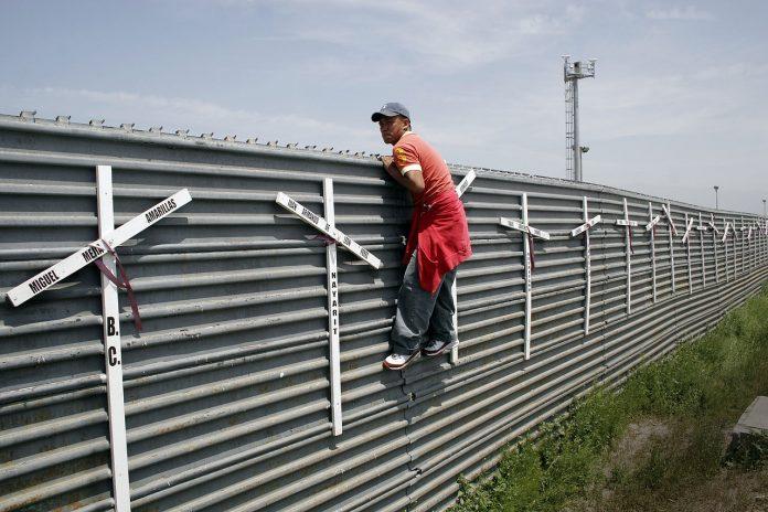 Homem escala muro na fronteira fronteira Tijuana-San Diego. As cruzes representam as mortes por tentativas fracassadas (Foto: Tomas Castelazo/Wikimedia)