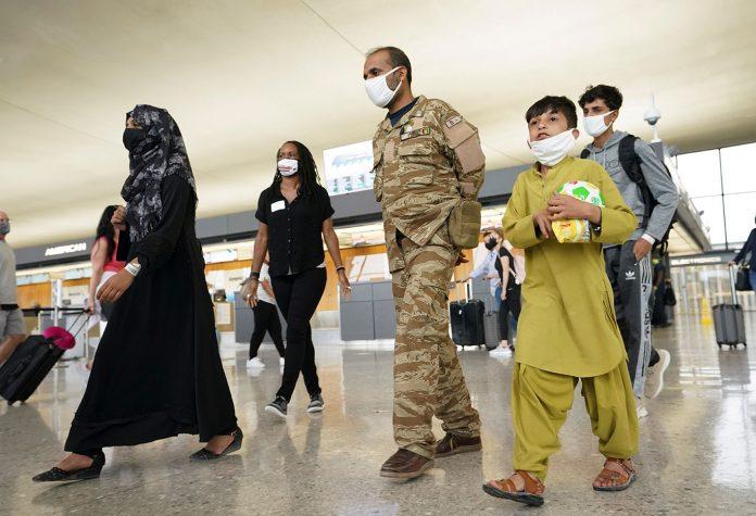 Família de afegãos caminha em direção a um ônibus que leva refugiados a um centro de processamento após sua chegada ao Aeroporto Internacional de Dulles, Virgínia (Foto: REUTERS/Kevin Lamarque)