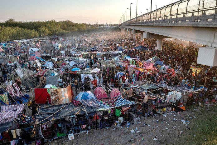 Imigrantes debaixo da Ponte Internacional Del Rio enquanto esperam para se entregar à Patrulha de Fronteira dos EUA e pedir asilo (Foto: REUTERS/Adrees Latif)